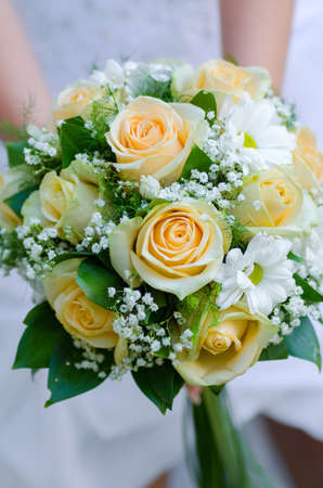 bride holding beauty wedding bouquet of yellow roses and white camomile