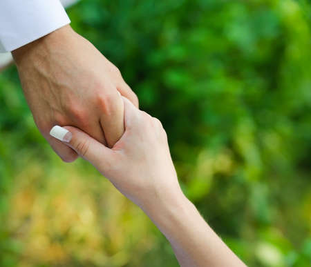 man hold a woman fingers by the hand  male assistance  Blur nature background