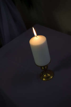 one light thick candle on a dark background with tall flame Stock Photo - 17562309