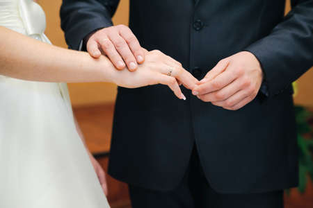 put on: wedding ceremony  Groom put on ring on a bride fingers Stock Photo