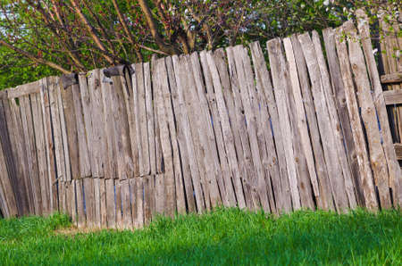 lopsided: old rural wooden fence of trees garden