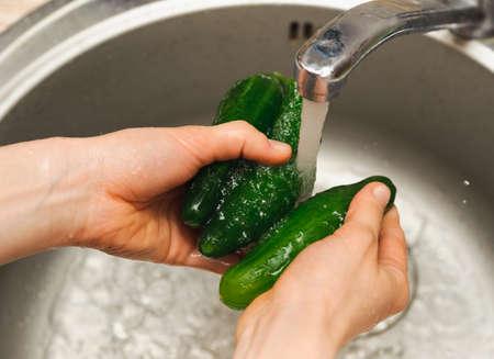 流水の下で緑のきゅうりを洗う女