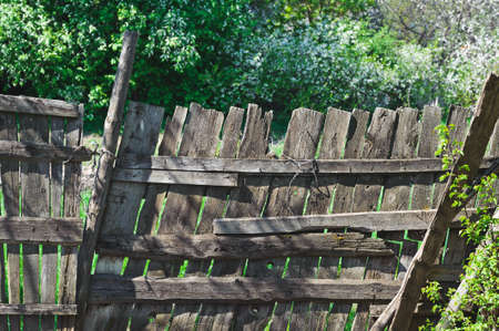 holed: old wooden lopsided fence. Time effect. Rural scene Stock Photo