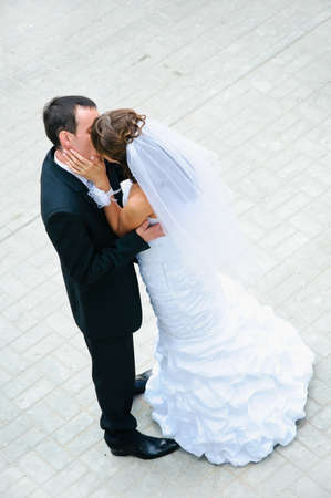 happy wedding couple standing, kissing and embracing photo