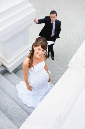 upward looking of smiling bride. Groom behind photo