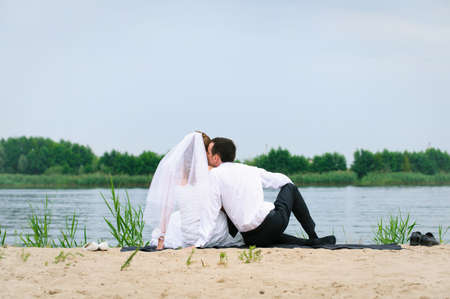 loving wedding couple sitting and kissing near river photo