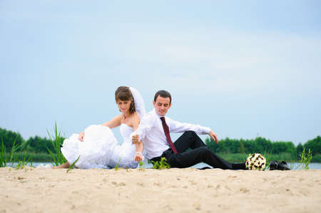 loving wedding couple sitting near water and strew sands photo