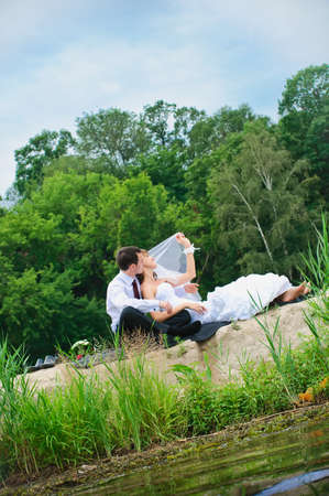 loving wedding couple sitting on sand near river photo