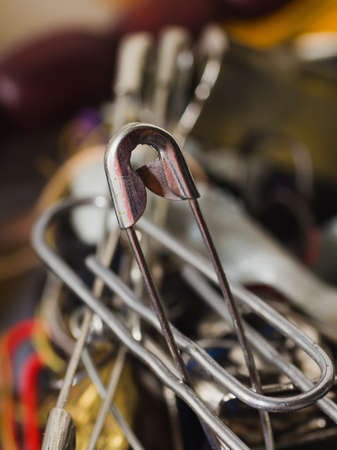 sartorial: closed safety pin on a blur backgrounds Stock Photo