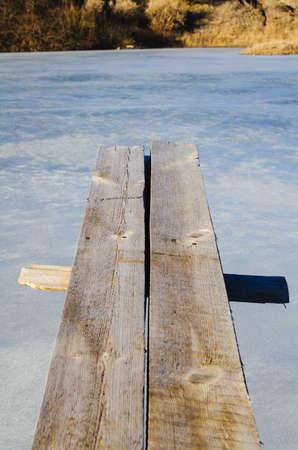 springplank: houten springplank overhang over ijs water Stockfoto