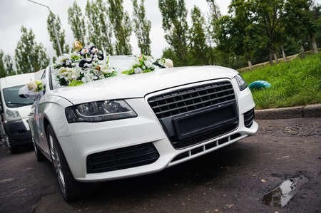 newlyweds traveling in a white decor wedding car procession  This is modified car in photoshop, unrecognizable and no potencial problems with trademark  No logo