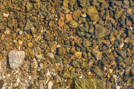rock bottom: many stones under clean transparent water of river  Motion blur water