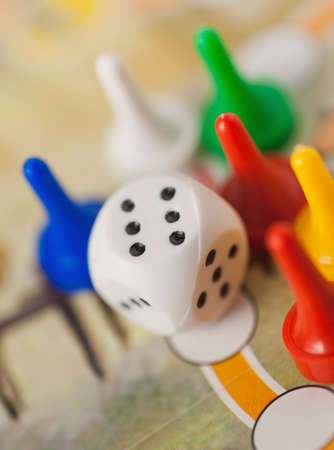 ivories: white dice cube near multicolored counter on game field Stock Photo