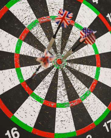 concurrent: old perforation dartboard with flags on darts. focus on center of target