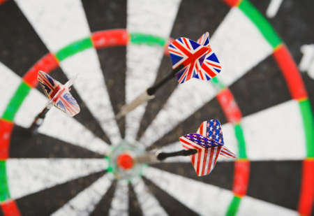 concurrent: old perforation dartboard with flags on darts. focus on flag