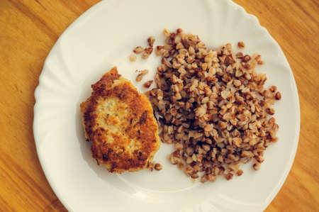 groats: economy food. rissole and buckwheat groats. warm toned Stock Photo