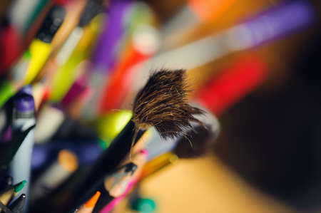 dishevelled: dishevelled paintbrush in a box of coloured pencils. soft selective focus and blur backgrounds