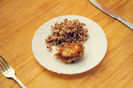 frugal: economy food. rissole and buckwheat groats. warm toned Stock Photo