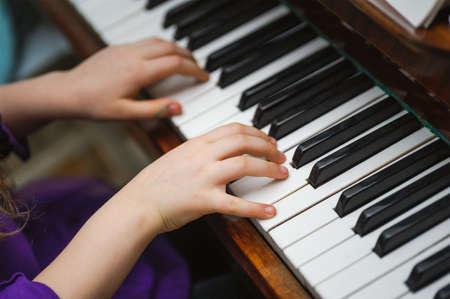 子供たちは、白いピアノのキーを手します。音楽を再生します。
