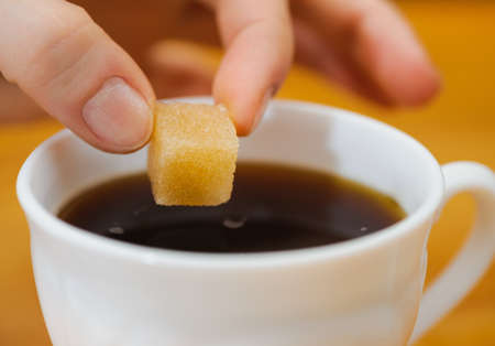 adding sugar: fingers hold a lump sugar piece over cup of tea. selective focus Stock Photo