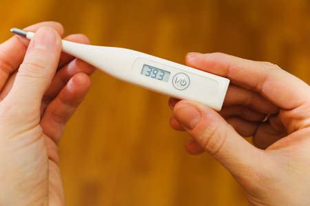 high temperature: hands hold thermometer with high temperature on a screen