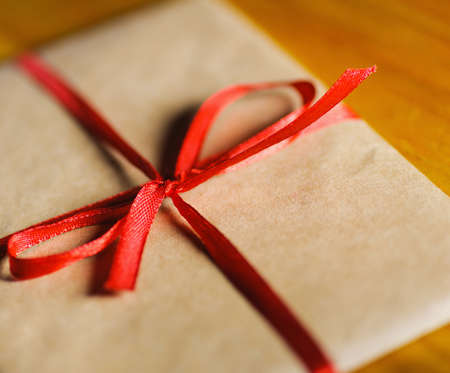 vintage envelope of kraft paper with red ribbon. Close-up selective soft focus technique
