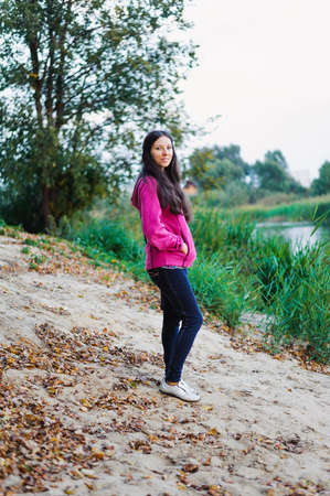unworried: young woman in casual clothing standing of pond shore Stock Photo