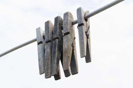 clothespegs: old wooden clothespegs hanging on rope. White sky backgrounds. Selective focus