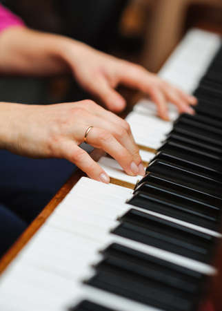 musical score: woman hands on a piano key. Playing music. selective focus technique