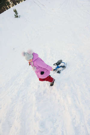 girl go uphill and drag her snow-scooter Stock Photo