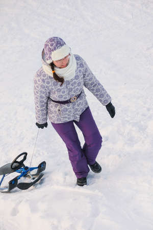 woman go uphill and drag snow-scooter on white snow backgrounds Stock Photo