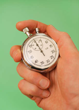 hand holding a stopwatch on green backgrounds