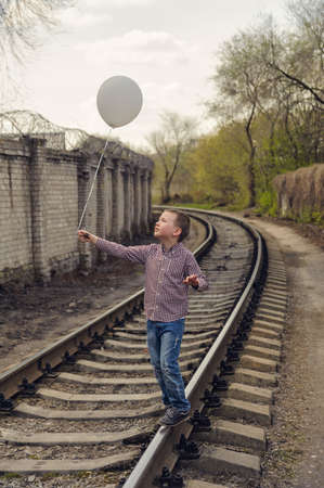 kid walk on rails with a balloon on a string in his hand Stock Photo