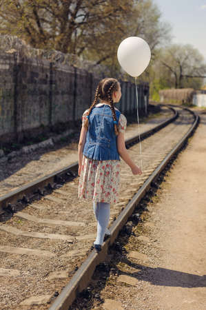 girl with pigtails walk on rails with a balloon on a string in her hand Stock Photo