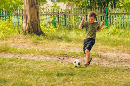 running boy playing with the ball on rural backgrounds