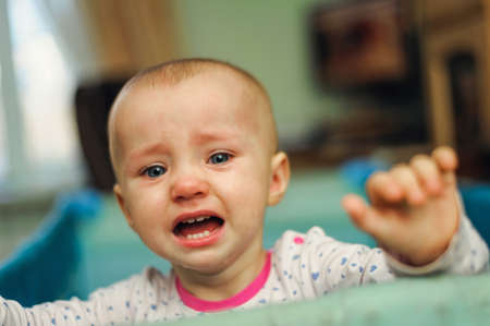 tearful child standing in playpen