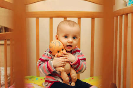 pretty child with a doll sitting in a cot