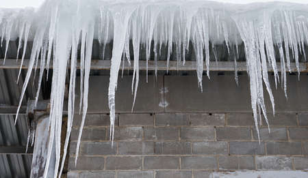 big icicles overhanging on a roof 版權商用圖片