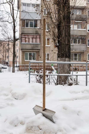 a shovel inserted in the snow on background of a house
