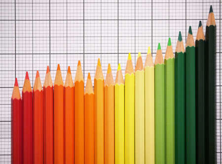 coloured crayons lay on checkered paper like an increasing business chart, bunte Stifte liegen in Form einer aufsteigenden Kurve auf kariertem Millimeter-Papier Stock Photo