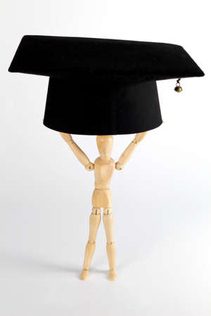 a wood figure is lifting a mortarboard Stock Photo