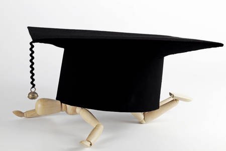 doctoral: a wood figure is breaking down under a mortarboard