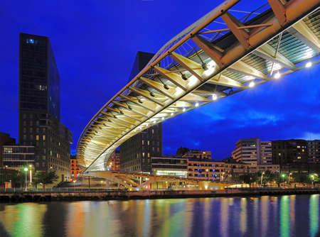 Bilbao, Baskia, Spain - bridge Zubizuri river Ria del Nervio at blue hour w colorful reflections in the water