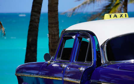 oldtimer taxi car in front of palm trees at the caribbean sea in cuba