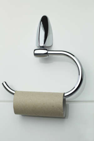 a toilet roll holder with an empty roll only, metaphor for selfish behavior, a holder for toilet paper with an empty roll, metaphor for selfish or lack of sustainable behavior