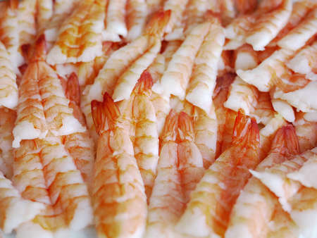 lots of fresh red prawns as known from sushi are presented on a dish
