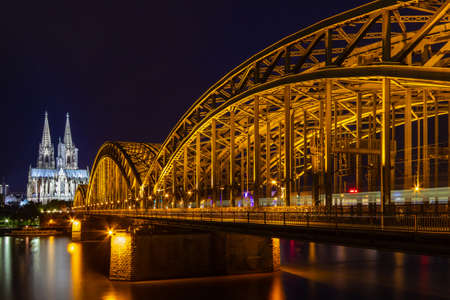 the cathedral from Cologne with the Hohenzollern bridge at the Rhine river at night, beautiful illumination