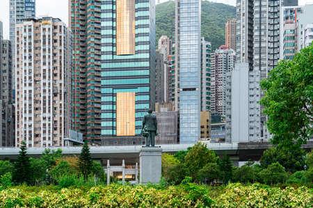 Hong Kong, Sun Yat Sen founder statue in Sai Ying Pun watches Hong Kong Island w highway in front of the downtown buildings Stok Fotoğraf