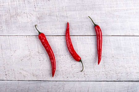 Ripe red chilli peppers on a wooden horizontal surface