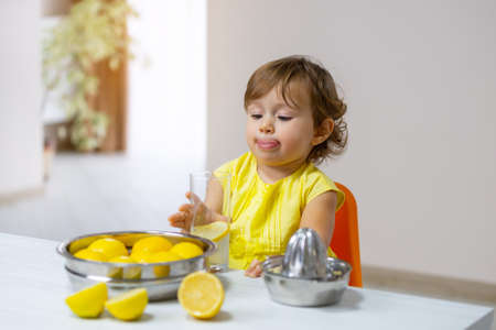 A little girl in a yellow dress tastes the cooked lemonade from a glass cup and licks herself